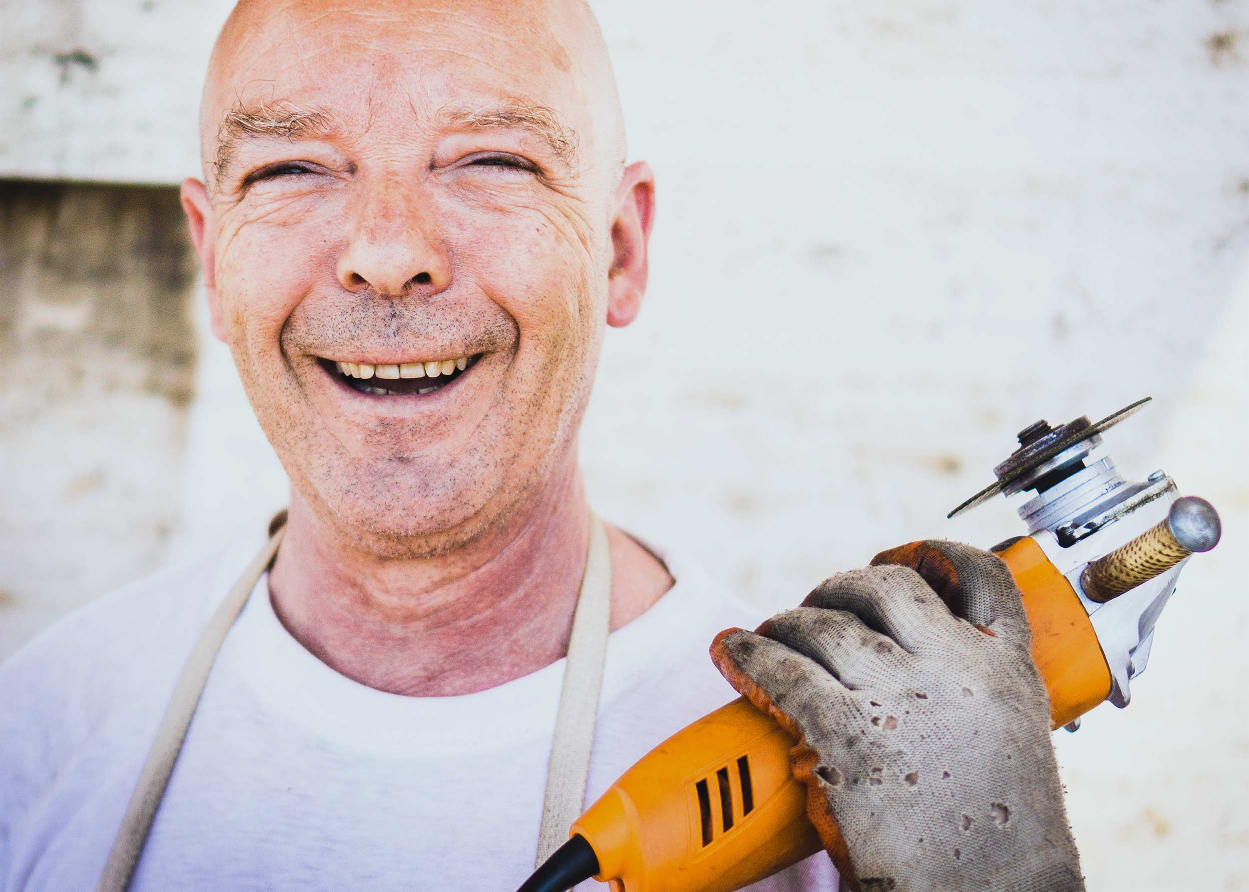 A smiling worker holding a power tool